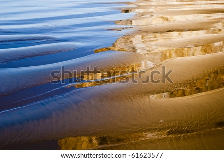 Reflection of sky and rocks in wet sand - stock photo