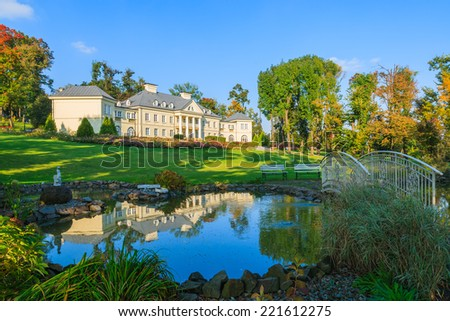 Reflection of Smilowice palace in small pond located in a green park, Poland - stock photo