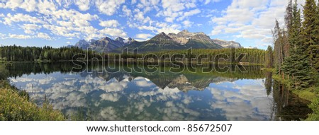 Reflection of snow mountains in smooth water of Herbert Lakes (Banff National Park, Alberta, Canada)