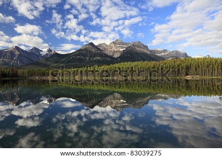 Reflection of snow mountains in smooth water of Vermillion Lakes (Banff National Park, Alberta, Canada)