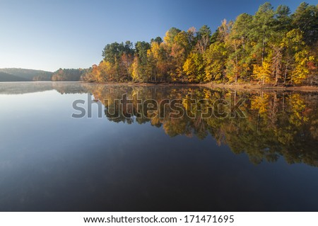 Reflection of sunrise and autumn color in still water lake - stock photo