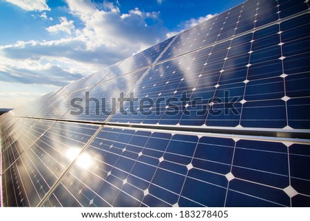 Reflection of the cloudy sky on the photovoltaic modules - stock photo