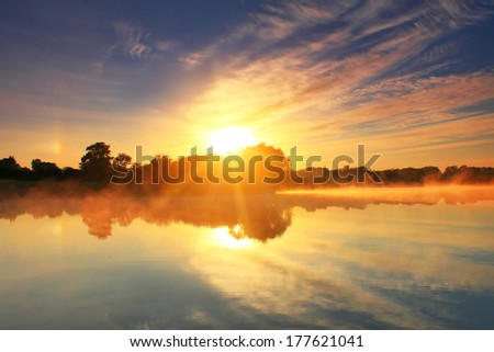 Reflection of the dawn sky in a lake - stock photo