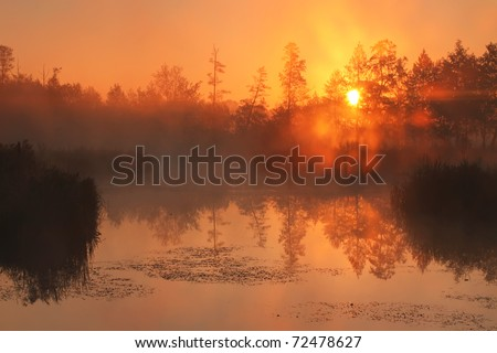 Reflection of the first rays of dawn sunlight in the lake - stock photo