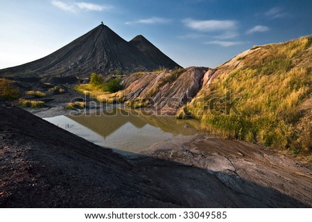reflection of the hills of old colliery in small lake in Ukraine - stock photo