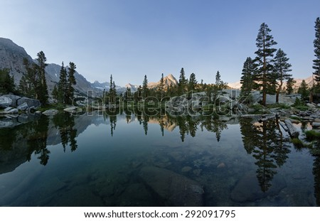reflection of the mountains and trees in blue lake in the morning - stock photo