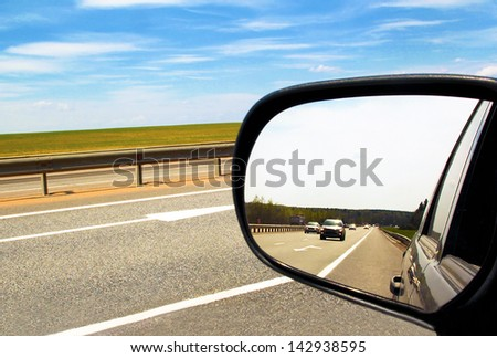 Reflection of the movement of vehicles in the car mirror in the summer cloudy weather. - stock photo