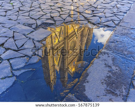 Reflection of the Orvieto cathedral in a water puddle, Tuscany, Italy - stock photo