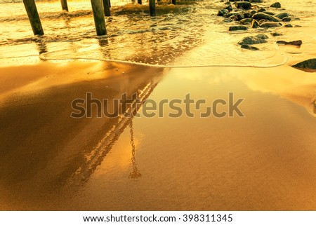 Reflection of the pier on the beach at golden sunset