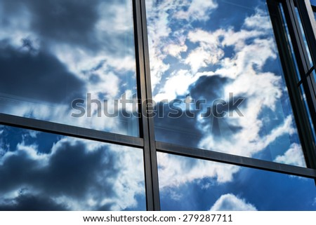 Reflection of the sky and clouds in the windows of a building - stock photo