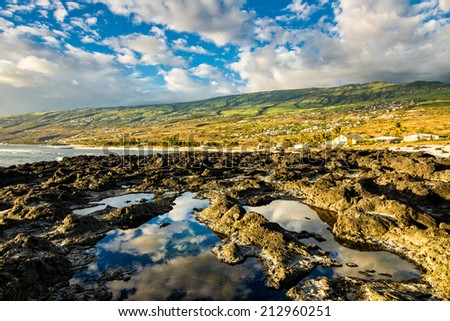 Reflection of the sky on tide pools and coast of la Reunion island - stock photo