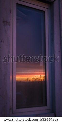 Reflection of the sunset at Oresund between Denmark and Sweden , on a window on an old fisherman cottage
