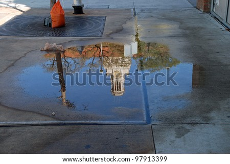 Reflection of the University of Texas main building tower on a puddle left from the rain during the SXSW 2012. - stock photo