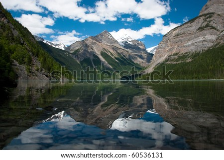 Reflection of tree covered and snow peaked Mt. Robson in Kinney Lake on a summer's day. - stock photo