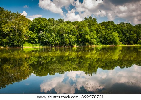 Reflection of trees and clouds in the Potomac River, at Balls Bluff Battlefield Park in Leesburg, Virginia - stock photo