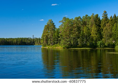 Reflection of trees in lake in Finland - stock photo