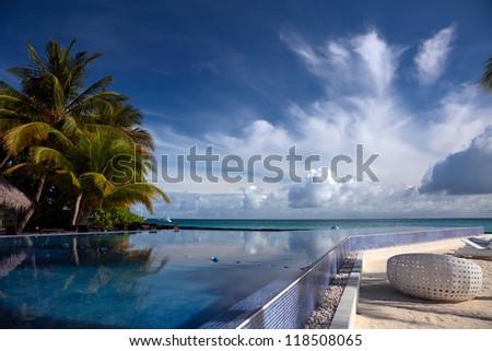 Reflection of trees in the pool water on Kuramathi Island, Maldives, Rasdhoo Atoll. - stock photo