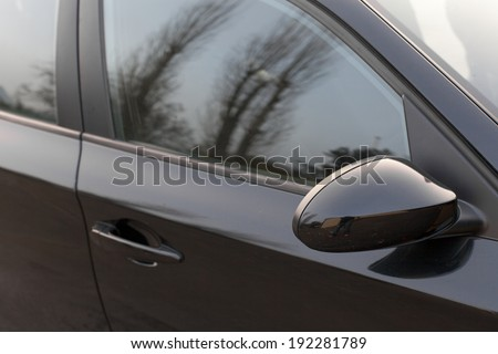 Reflection of trees in the window of a car - stock photo