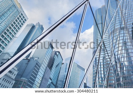 Reflection of urban skyline on modern office building - stock photo