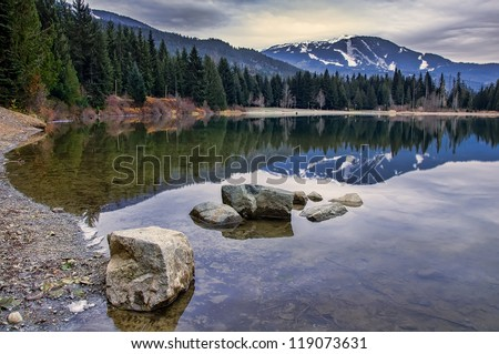 Reflection of Whistler mountain in pond with rocks - stock photo
