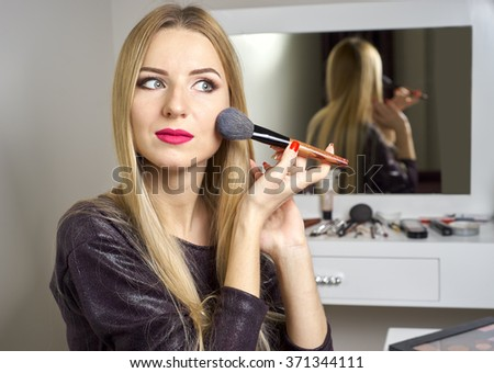 Reflection of young beautiful woman applying her make-up - stock photo