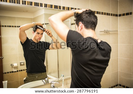 Reflection of Young Man Bushing Hair in Bathroom Mirror Getting Ready to Go Out - stock photo