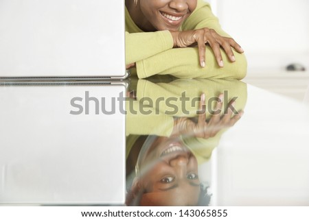 Reflection of young smiling businesswoman with laptop on table - stock photo