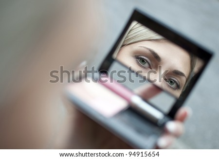 Reflection of young woman eyes visible in cosmetic mirror - stock photo