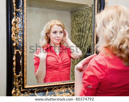 Reflection of young woman in a big mirror - stock photo