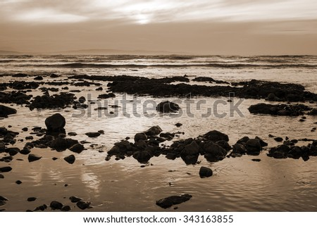 reflections at rocky beach near ballybunion on the wild atlantic way ireland with a beautiful sunset in sepia - stock photo