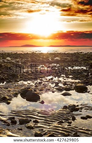 reflections at rocky beal beach near ballybunion on the wild atlantic way ireland with a beautiful yellow sunset - stock photo