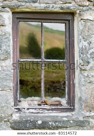 Reflections in an old scottish crofters cottage window - stock photo