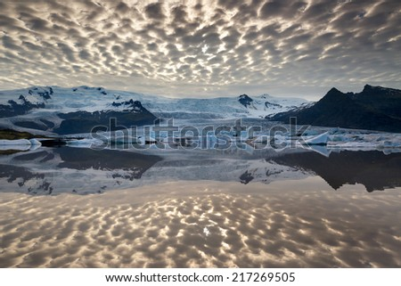 Reflections in Fjallsarlon lagoon in Iceland, by sunset - stock photo
