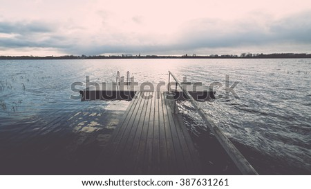 Reflections in the calm lake water with dramatic clouds and  with boardwalk- vintage effect