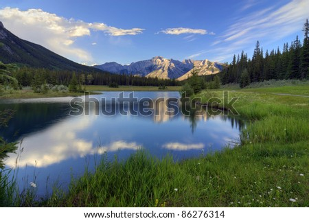Reflections into Cascade Ponds near Banff in Banff National Park Canada. These picturesque ponds are surrounded by the Rocky Mountains. - stock photo