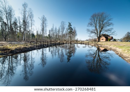 reflections of country house in the pond with trees and blue sky - stock photo