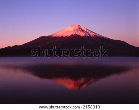Reflections of Mount Fuji in a still early morning lake - stock photo