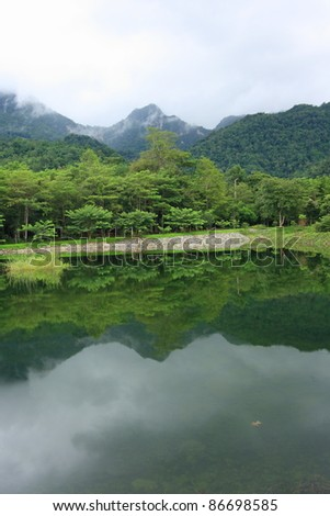 Reflections of mountain and forest in lake, Thailand - stock photo