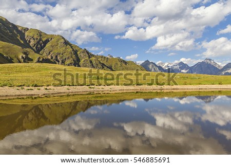 Reflections of mountains and clouds in a mountain lake, in the Caucasus Mountains, in Georgia.
