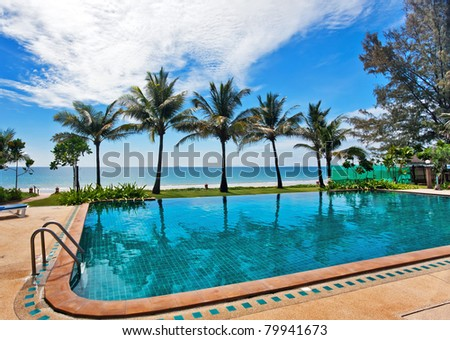 reflections of palms in the pool under blue sky - stock photo