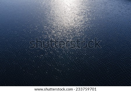 reflections of sun in deep blue water - stock photo