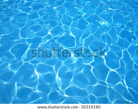 Reflections of sunlight on clear blue water - stock photo