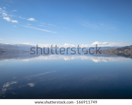 Reflections on a Still Lake in Springtime - stock photo