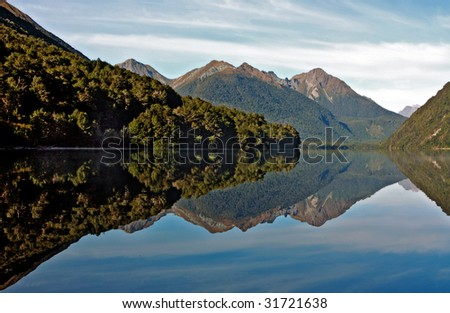 Reflections with New Zealand mountains and lake - stock photo