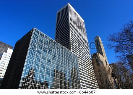 Reflective corporate buildings on a clear day in manhattan - stock photo