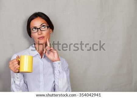 Reflective female holding mug and wondering with finger on cheek and formal shirt while looking up on grey texture background - copy space
