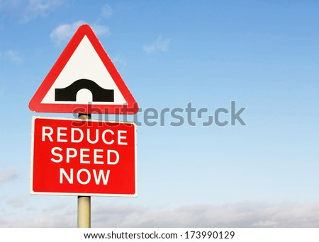 Reflective metallic 'hump backed bridge' and 'Reduce speed now' sign, isolated on a blue sky background.  - stock photo
