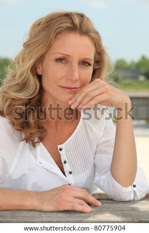 Reflective woman with long blonde hair sitting outside - stock photo