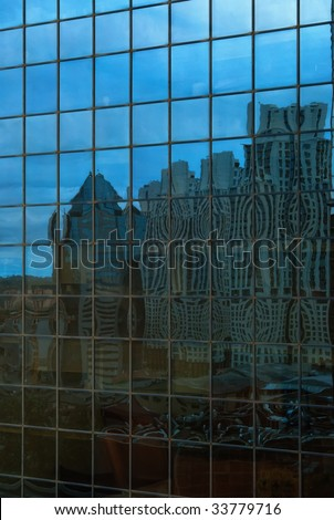 Reflexion of a modern district in windows of office building - stock photo