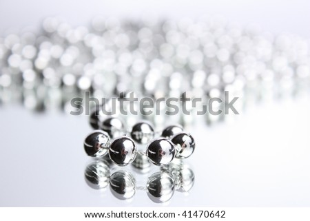 Reflexion of a silver beads in a mirror